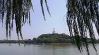 Pagoda berwarna putih di gunung Bunga Giok tampak dari seberang danau