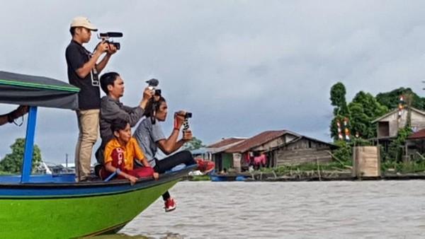 Kegiatan memburu foto pesut mahakam yang banyak hilir mudik di sungai desa Pela yang menghubungkan antara Danau Semayang dan Sungai Mahakam.