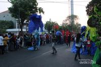 Warga yang menayksikan di sepanjang jalan tak henti-hentinya mengabadikan peserta karnaval.