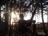 Bersantai di atas hammock sambil menatap ombak yang airnya menguning diterpa sinar matahari senja