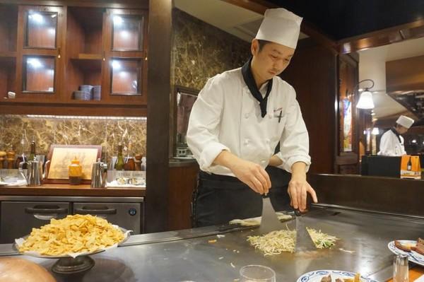 Chef secara langsung memasak sayur dan daging di depan tamunya
