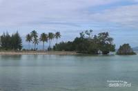 Pantai yang tenang dengan air laut yang tampak biru dan jernih