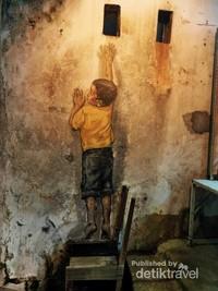 Lukisan anak yang naik ke atas kursi seakan ingin mengintip dari sebuah lubang di atasnya.