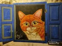 Lukisan kucing yang melongok ke luar jendela.