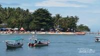 Para pengunjung sedang bersantai ria di pantai yang berpasir putih