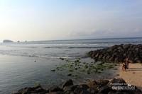 Ombak yang tenang menerpa pasir putih Pantai Candidasa, Karangasem, Bali