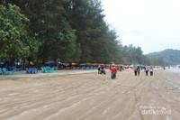 Di pinggir pantai dekat pepohonan terdapat banyak warung yang menjual makanan dan minuman .