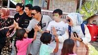 para volunteer melakukan bakti sosial dengan membagikan perlengkapan sekolah kepada anak-anak Pulau Salissingan.