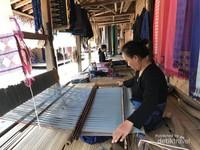 Perempuan warga Baduy Luar sedang menenun di teras rumah