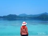 Memandang hamparan gradasi laut biru dan bukit hijau di sepanjang batas laut