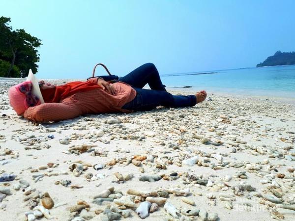 Berbaring di hamparan pasir sambil mendengarkan lagu-lagu favorite
