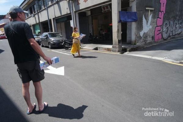 Para turis menggunakan peta untuk mencari street art yang iconik di Armenian street