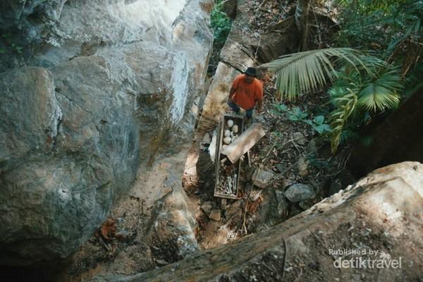 Tampak dari atas tebing gua sebuah peti terbuat dari kayu dengan tumpukan tengkorak