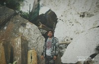 APeti jenazah terbuat dari kayu yang telah lapuk dijejer dengan posisi berdiri bersandar pada bongkahan batu besar