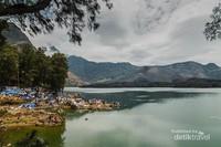 Tepian danau Segara Anak yang dipenuhi tenda-tenda dengan pemndangan gunung Baru Jari