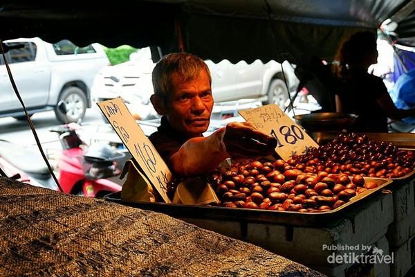 Pedagang Muslim sedang memberikan sa-ke, sejenis biji kluwih kepada pembeli