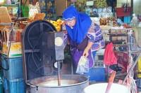 Seorang ibu-ibu sedang memasak Sa-ke dengan alat khusus