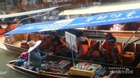 Pedagang yang menawarkan barang dagangan ke perahu wisatawan