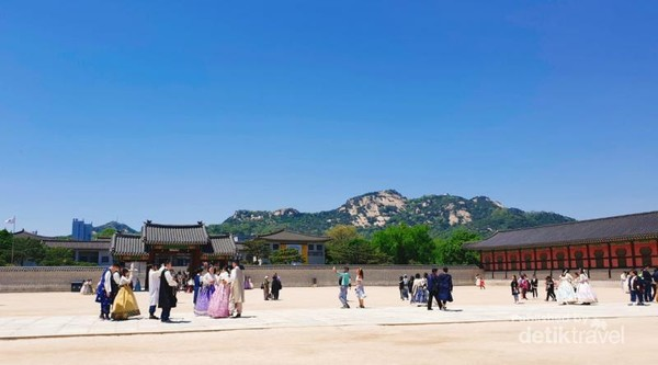 Para wisatawan menggunakan pakaian khas Korea Seatan mengantri berfoto demi latar menara istana yang instagramabele.