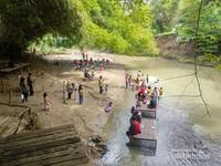 Pengunjung menikmati makanan dan anak-anak bermain di pinggir Kali Gawe