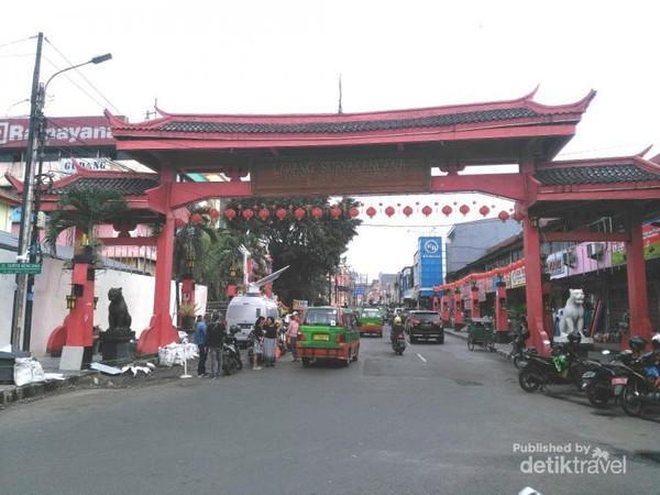Lawang atau Gerbang Surya Kencana yang berada di depan pintu masuk utama (selatan) Kebun Raya Bogor. Gapura yang mengadopsi budaya etnis Tionghoa ini diresmikan pada Februari 2016. Masyarakat Tionghoa sudah mendiami wilayah ini sejak zaman Kolonial, tepatnya setelah peristiwa Geger Pecinan di Batavia (Jakarta) tahun 1740. VOC menempatkan etnis Tionghoa di kawasan ini agar tidak mempengaruhi warga pribumi untuk turut memberontak kepada VOC, selain juga bagian dari politik Devide et Impera. Konon kawasan ini masih dalam jangkauan meriam VOC yang mengelilingi Istana Bogor, sehingga kalau kembali terjadi pemberontakan dapat dengan mudah ditumpas.