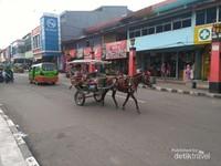Delman, transportasi tempo dulu di zaman kekinian yang mengaspal di Jalan Surya Kencana. Dahulu jalan yang melintasi Kampung Tionghoa Surya Kencana ini merupakan Jalan Raya Pos Daendels yang menghubungkan Anyer di Banten hingga Panarukan di Jawa Timur. Jalan Raya Pos ini menghubungkan loji-loji militer Prancis di sepanjang pantai utara Jawa (1100 km) guna mengantisipasi serangan Inggris. Keseluruhan Jalan Raya selesai dibangun setahun saja pada 1808, menggunakan tenaga kerja Rodi yang menelan korban jiwa dalam jumlah besar.