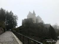 Jalanan menanjak menuju kastil yang diselimuti kabut