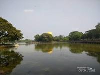 Bayangan pagoda yang bersembunyi dibalik pepohonan tampak di cermin air danau.