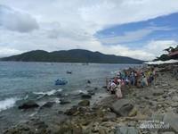 Banyak pengunjung turun  menikmati pantai dan lebih dekat dengan air laiut.