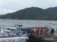 Pengunjung datang dan pergi dengan kapal-kapal motor kecil.