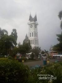 Foto Jam Gadang dari kejauhan di balik pepohonan taman kota Bukit Tinggi.