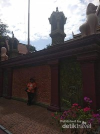 Berfoto di dinding pagar yang mengelilingi kawasan Wat Phnom.