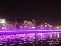 Jajaran rumah tumpangan yang penuh wisatawan yang ingin menikmati suasana tepi sungai di  malam hari.