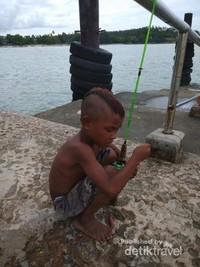 Seorang anak asik mempersiapkan pancingannya.