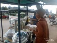 Seorang pedagang kue sudah memulai aktivitasnya sejak pagi