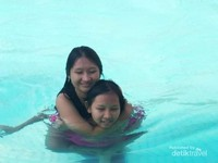 Kakak adik boleh bergendong-gendongan bebas dalam kolam renang.