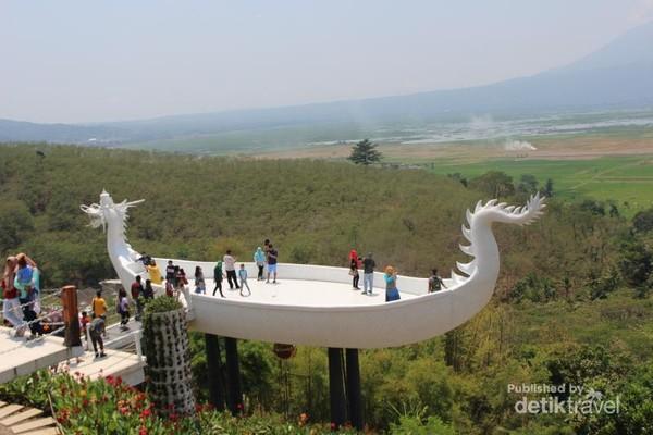 Dek berbentuk perahu dengan kepala naga menjadi tujuan pegunjung untuk berfoto dan menikmati pemandangan.