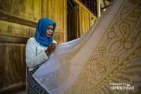 Pengrajin batik sedang nyanthing kain batik
