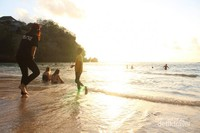 Para wisatawan yang masih asik bermain air di bawah sinar matahari yang terbenam