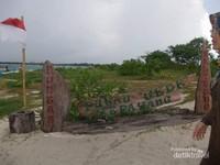 Nama pulau yang terbuat dari papan kayu di salah satu sudut pantai.