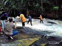 para wisatawan bergantian mengabadikan momen uji nyali menyeberangi air terjun kandua raya.