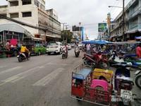 Aktivitas saat pagi hari di jalan depan pasar. Banyak kendaraan lalu lalang.