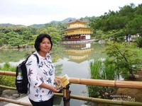 Berfoto di tepian danau dengan latar belakang danau dan Kuil Kinkaku.