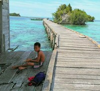 seorang anak pulau papan sedang asik bermain sendirian