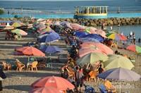 Kedatangan pengunjung ditandai dengan banyaknya payung-payung tempat bersantai pada tepi pantai.