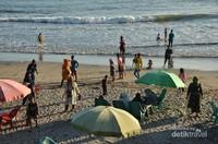 Tepian pantai kembali ramai oleh wisatawan yang bermain ombak, anak-anak bermain, dan orang dewasa yang mengabadikan lewat foto.