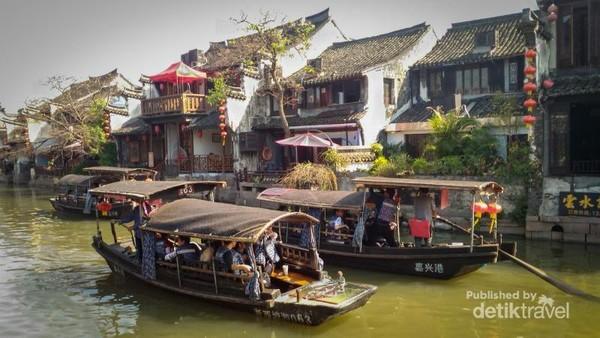 Pemandangan kapal-kapal tua berlayar dengan background rumah-rumah tradisional cina