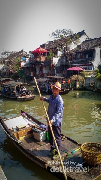 Salah seorang pengemudi kapal mendayung dan mengarahkan perahu di kanal