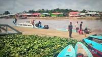 Tampak penumpang baru turun dari perahu motor yang baru saja bersandar.