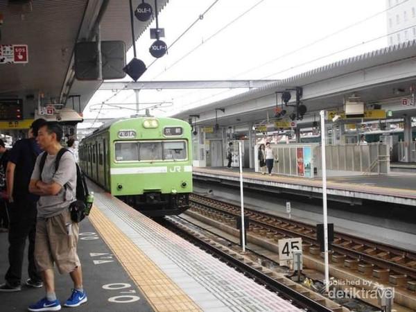 Tampak kereta api yang sedang memasuki stasiun siap menurunkan serta mengangkut penumpang.